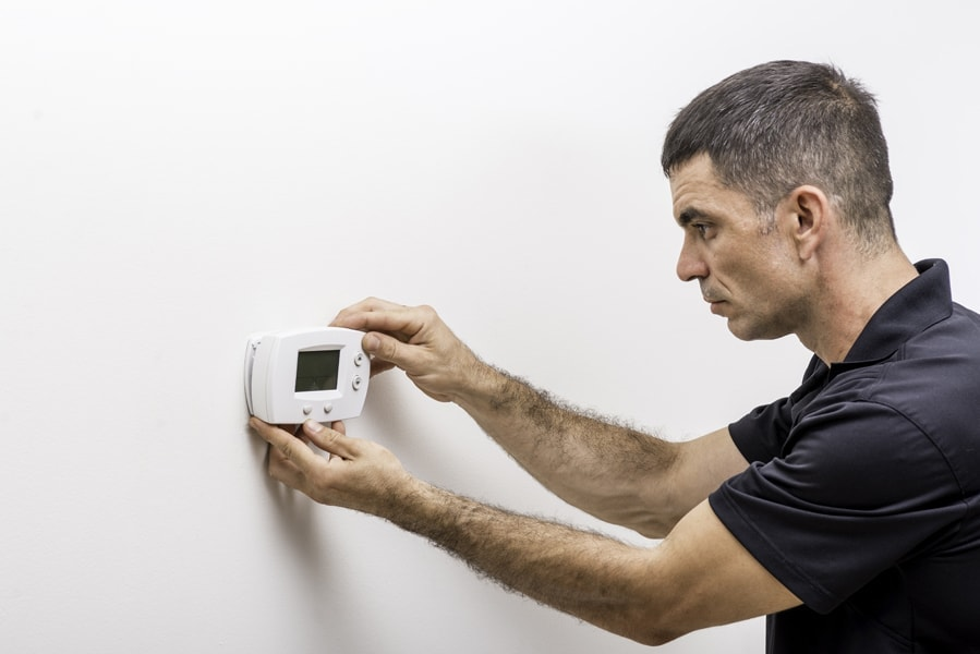 Hvac technician installing faceplate on a digital thermostat