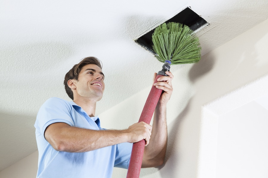 Man Cleaning Air Ducts to help eliminate Mold