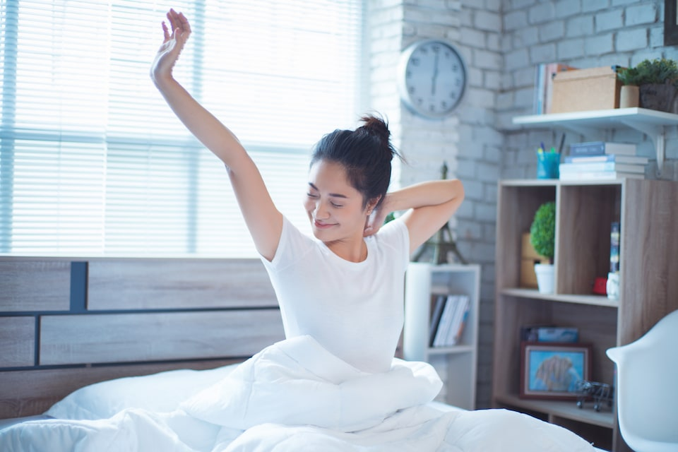 Woman waking up after sleeping well with AC on in home