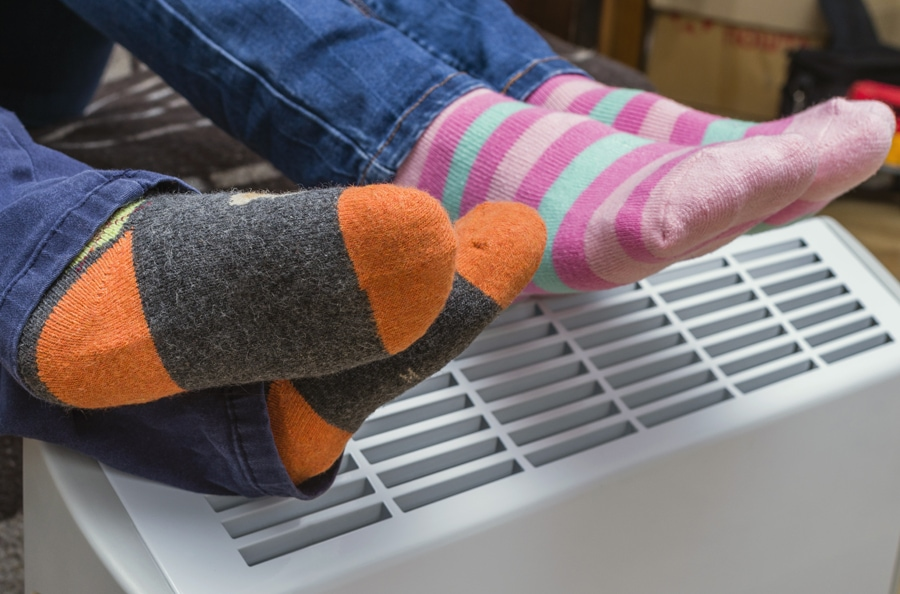 Homeowners relaxing and staying warm with their feet on their air ducts after following the furnace maintenance tips.