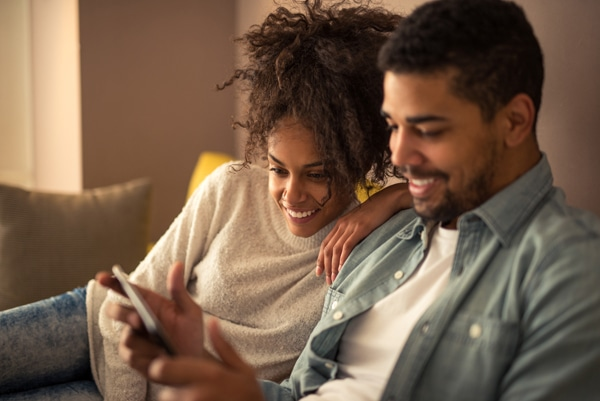 African american couple going over their heating bill on a tablet. How to save money on your heating bill this winter.
