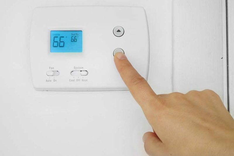 A hand lowering the temperature on a thermostat | Is It Normal for My AC to Turn On and Off? | Fort Collins, CO