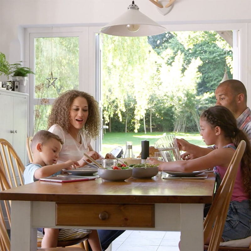 A family enjoying a meal around a table | Video - Indoor Air Quality Affects Your Family's Health